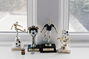 A grouping of soccer trophies on a windowsill