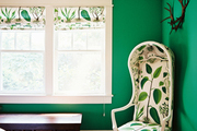 A botanical-print chair in a bedroom with green walls and a wallpapered ceiling