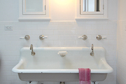A vintage trough sink in an all white bathroom