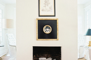 A white mantel adorned with framed art