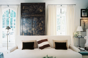 A white couch and a chinoiserie cabinet in a neutral living space