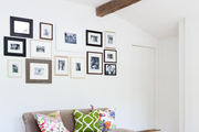 Framed photographs hung above an armless couch with patterned pillows