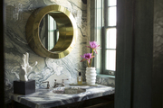 A bathroom filled with marble and a round mirror