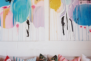 Art above a couch with multicolored pillows