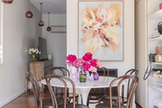 Pink flowers are arranged on a dining table with artwork on the wall.