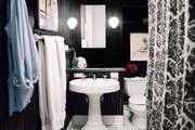 Black walls paired with a white pedestal sink