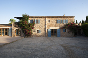 The stonework exterior of a Majorca home, accented by blue shutters