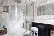 A subway-tiled bathroom with a glass-enclosed shower and dark wood vanity beneath a trough sink