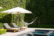 A hammock, chaises, and an umbrella beside a swimming pool