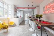 A contemporary kitchen with white walls and a neon sign.