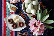 A bowl of fresh eggs and chocolate treats adorn an Easter tabletop