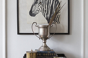 A Sharpie sketch of a zebra above an old trophy on a black table