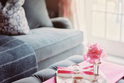 A gray tufted ottoman holds a pink wool throw and a silver tray with tea.