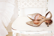 A pair of gold shoes on a white chair