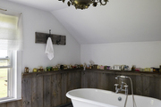 Aged wood wainscot surrounding claw foot tub.