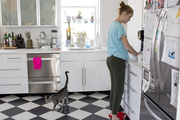 A teenage girl at her kitchen counter with black-and-white tile floors and IKEA cabinetry