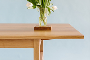 A bouquet of tulips on a wooden dining table.