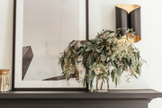 A detail of a mantel and a black and gold wall sconce.