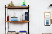 An iron-and-wood bookcase separating a living and dining room