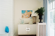 Beach-themed artwork in a white living space