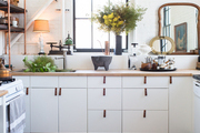 An Ikea kitchen with custom details such as leather pulls, black baseboards, and shelves with copper piping