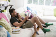 Father and daughter read together on a large sectional sofa