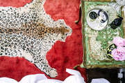 An antique end table is set on a cheetah print rug.