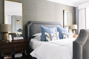 An upholstered bed in a gray-toned master bedroom