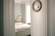 A convex mirror in the entrance to a bedroom