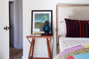 A guest room with an upholstered headboard and a colorful quilt