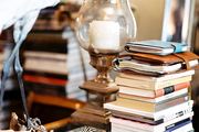 A stack of books and a hurricane lamp on a glass tabletop