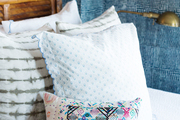A detail of a white bed with a colorful pillow.