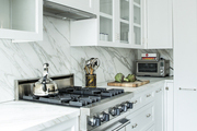 A stainless stovetop and range in a clean white kitchen