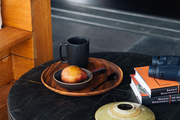 Breakfast and books atop vintage round black table.