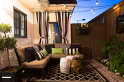 Wonderfully lit outdoor patio area with hanging lights and comfy outdoor seating.