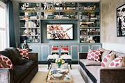 A living space with matching gray couches and blue built-in bookshelves backed by mirror