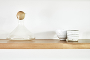 A shelf with two ceramic cups and a decanter sitting on top.