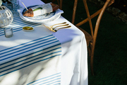 A blue and white striped table runner drapes over a Bastille Day dinner table in Charleston, South Carolina