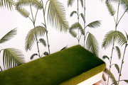 Palm-frond wallpaper and a green bench in a dressing room