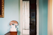An antique wooden chair and a gold-frame mirror against blue walls