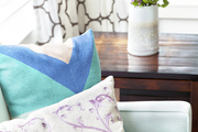 Geometric and embroidered pillows next to a vase of purple flowers and patterned curtains in Malibu, California