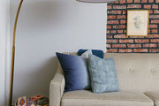 A large gold lamp hovers over a sofa with blue pillows