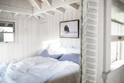 White bed in a room with exposed beams