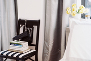 A striped black fretwork chair flanked by gray curtains