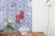 A colorful wallpaper panel hung in a dining space