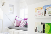Built-in bookshelves and a sunny window seat in a cheery kid's room