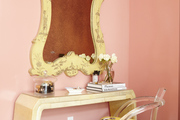 Framed mirror and matching yellow furniture in a pink-walled room.