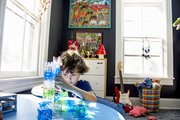 A boy in his bedroom with chalkboard walls and a low play table