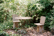 A table and chairs tucked among mature landscaping