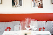 Nautical artwork above a red banquette